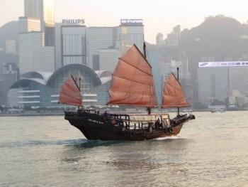 A traditional sampan still sailing along in the Hong Kong harbor.